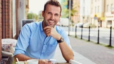 man smiling while sitting outside cafe