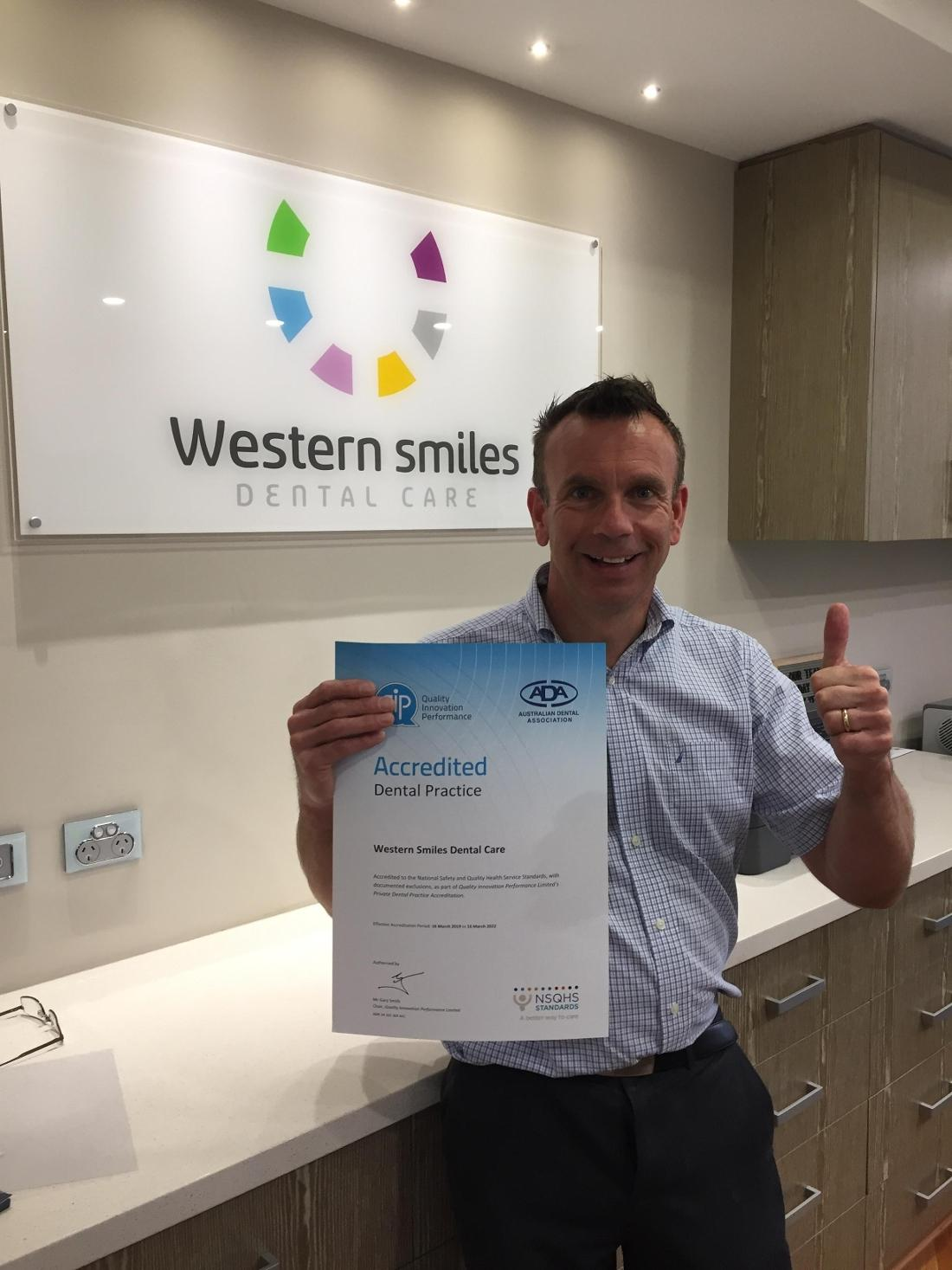 Dr Peter holding Western Smiles QIP accreditation certificate
