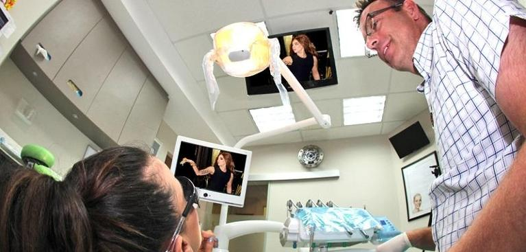 TVs above dental chairs with Dr Duke standing next to patient